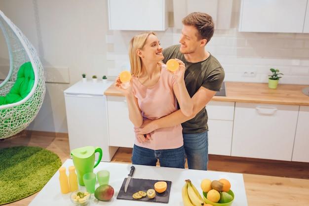 Młoda kochająca para bawi się organiczną pomarańczą podczas gotowania świeżych owoców w białej kuchni