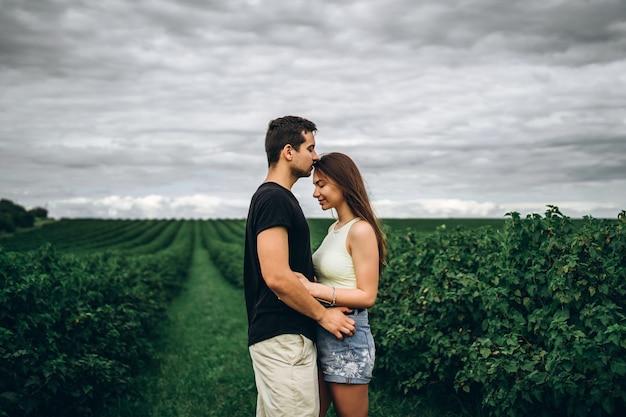 Młoda kochająca para delikatnie ściska na tle zielonych porzeczek. historia miłosna