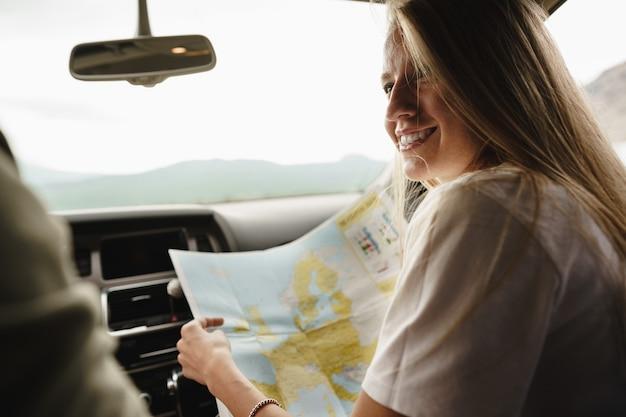 Młoda kochająca para na wycieczce samochodowej, korzystając z mapy w samochodzie
