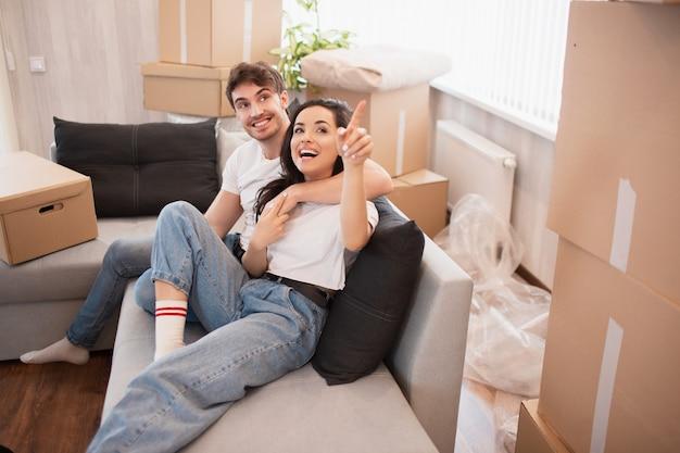 Młoda kochająca para przeprowadzka do nowego domu. koncepcja domu i rodziny. siedzą na kanapie i patrzą na swój nowy dom.