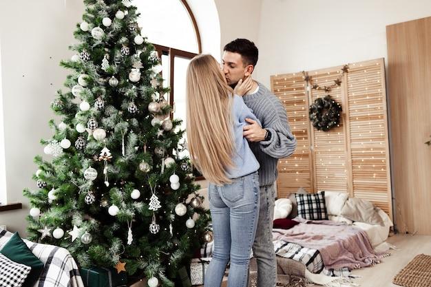 Młoda kochająca para razem dekoruje choinkę