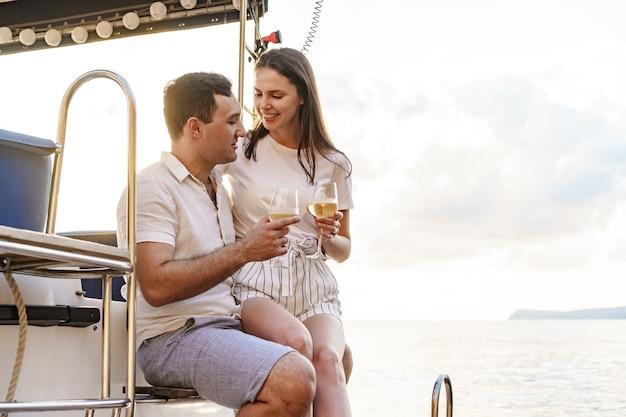 Młoda kochająca para siedzi na pokładzie jachtu i pije wino