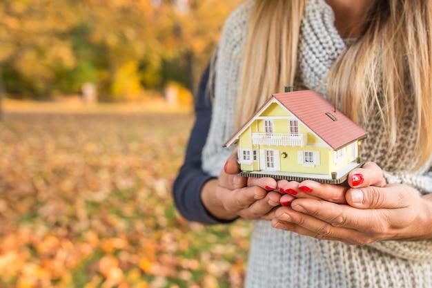 Młoda kochająca para trzymająca mały modelowy dom w jesiennym ogrodzie lub parku