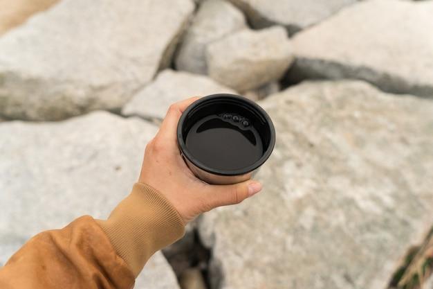 Młoda koczowniczka lub szukająca przygód kobieta w brązowej skórzanej kurtce trzyma filiżankę czarnej amerykańskiej kawy lub herbaty w kubku kempingowym lub kubku kempingowym
