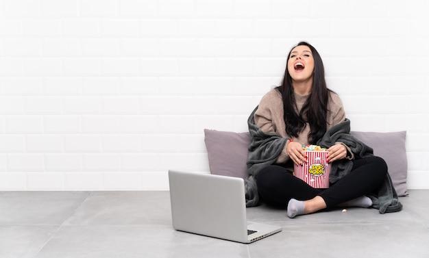 Młoda kolumbijka trzyma miskę popcornu i pokazuje film w laptopie krzyczący do przodu z szeroko otwartymi ustami