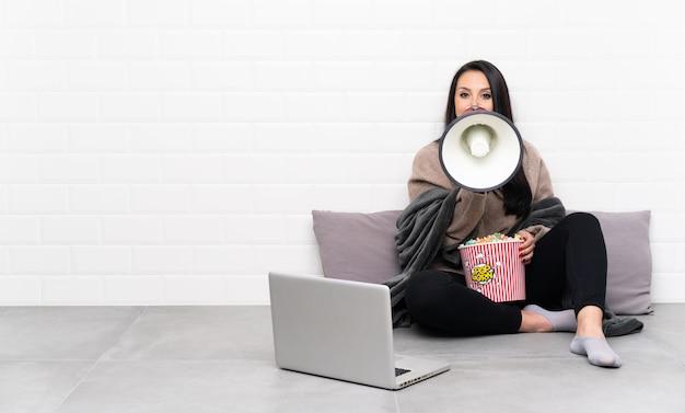 Młoda kolumbijka trzyma miskę popcornu i pokazuje film w laptopie krzyczący przez megafon
