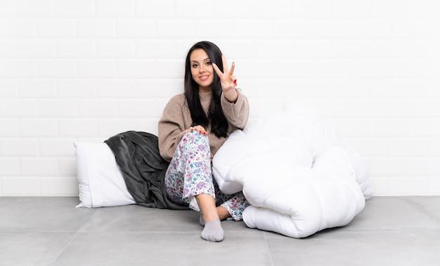 Młoda kolumbijka w piżamie w pomieszczeniu szczęśliwa i licząca trzy z palcami