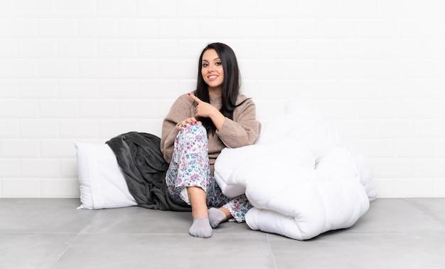 Młoda kolumbijka w piżamie w pomieszczeniu wskazująca na bok, aby przedstawić produkt