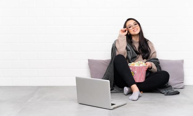 Młoda kolumbijska dziewczyna trzyma puchar popcorns i pokazuje film w laptopie z szkłami i szczęśliwy