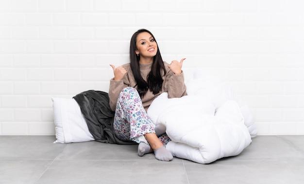 Młoda kolumbijska dziewczyna w piżamie w pomieszczeniu z kciuki do góry gestem i uśmiechnięte