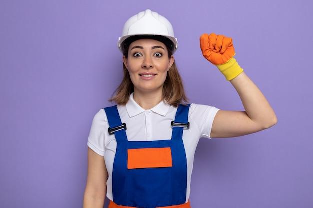 Młoda konstruktorka w mundurze budowlanym i kasku ochronnym w gumowych rękawiczkach szczęśliwa i podekscytowana podnosząca pięść stojąca na fioletowo