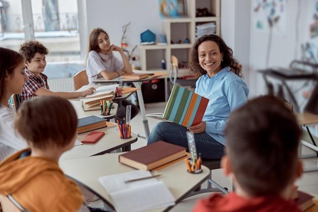 Młoda korepetytorka uczy czytać swojego ucznia. dzieci ze szkoły podstawowej siedzą na biurkach i czytają książki w klasie.
