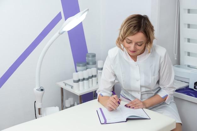 Młoda kosmetolog rejestrująca wyniki badań i uśmiechająca się w nowoczesnym gabinecie kosmetycznym