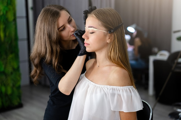 Młoda kosmetyczka dziewczynka kaukaski posiada model korekcji brwi