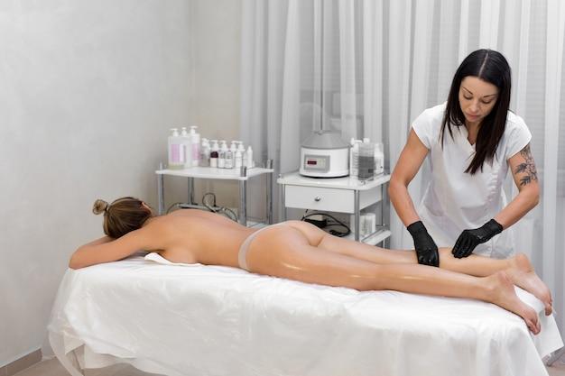 Młoda kosmetyczka wykonuje masaż kobiecie, masuje nogi olejkiem. masaż antycellulitowy w salonie spa.
