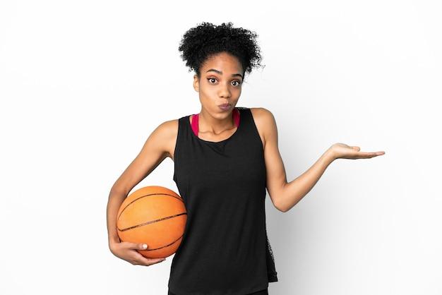Młoda koszykarz, latynoska kobieta na białym tle, mająca wątpliwości podczas podnoszenia rąk