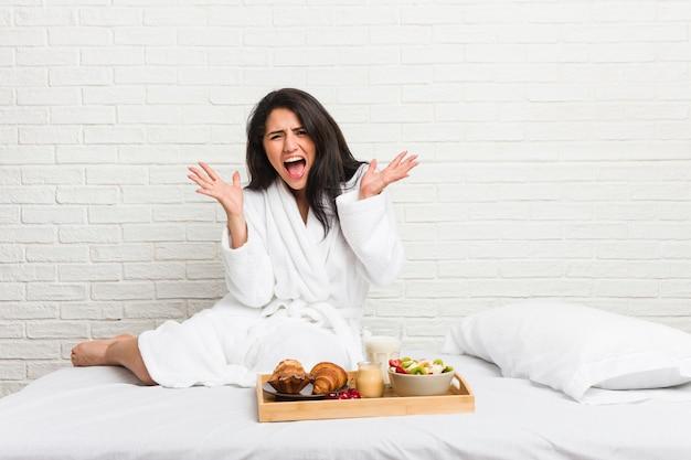 Młoda krągła kobieta je śniadanie na łóżku, świętując zwycięstwo lub sukces, jest zaskoczony i zszokowany.