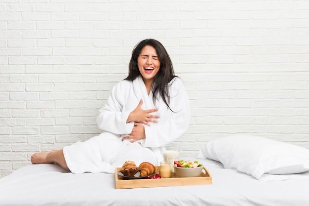 Młoda, krągła kobieta, jedząca śniadanie na łóżku, śmieje się radośnie i bawi się, trzymając ręce na brzuchu.