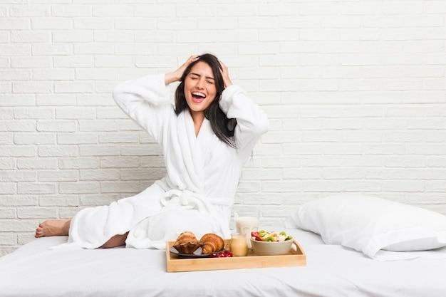 Młoda krągła kobieta, jedząca śniadanie na łóżku, śmieje się radośnie, trzymając ręce na głowie