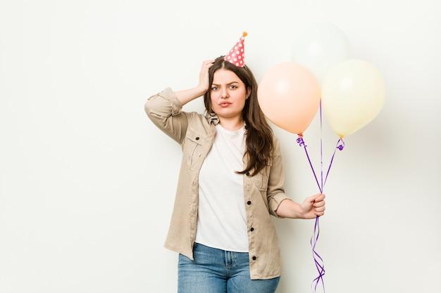 Młoda, krągła kobieta plus size świętująca urodziny, będąc w szoku, przypomniała sobie ważne spotkanie.