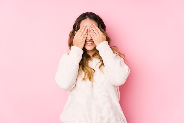 Młoda krągła kobieta pozuje na różowym tle na białym tle wady oczu rękami, szeroko się uśmiecha, czekając na niespodziankę.