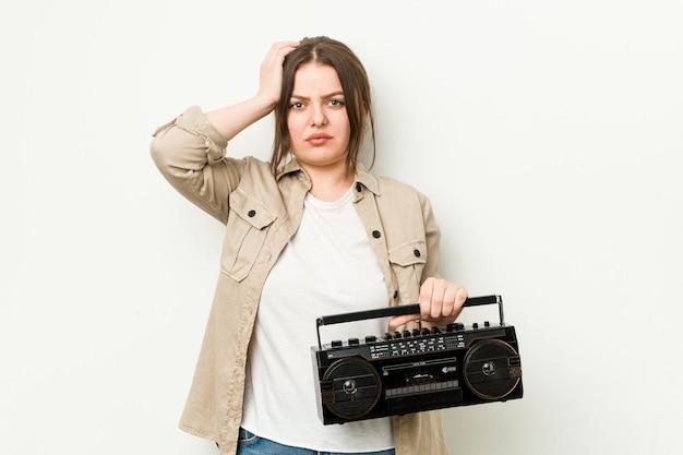 Młoda krągła kobieta trzymająca retro radio, wstrząśnięta, przypomniała sobie ważne spotkanie.
