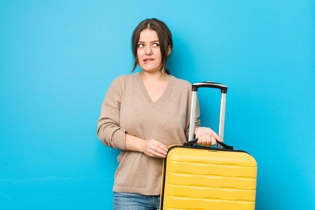 Młoda, krągła kobieta z walizką zdezorientowana, niepewna i niepewna.