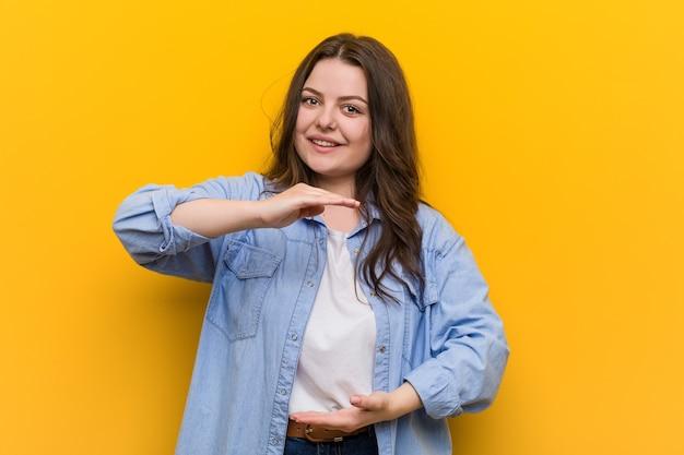 Młoda krągłe plus size kobieta trzyma coś obiema rękami, prezentacja produktu.