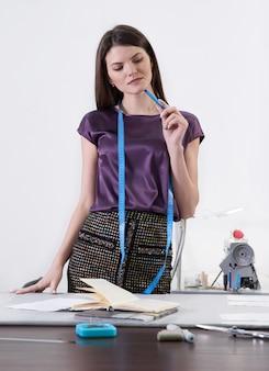 Młoda krawiecka w swoim warsztacie projektującym nowe ubrania, studio atelier