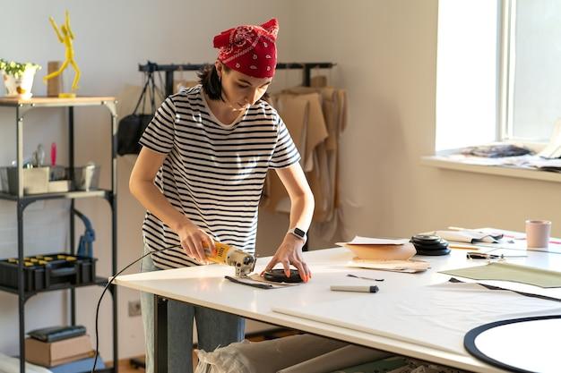 Młoda kreatywna dziewczyna projektanta wycinania wzorów do tworzenia kolekcji w profesjonalnym studiu warsztatowym