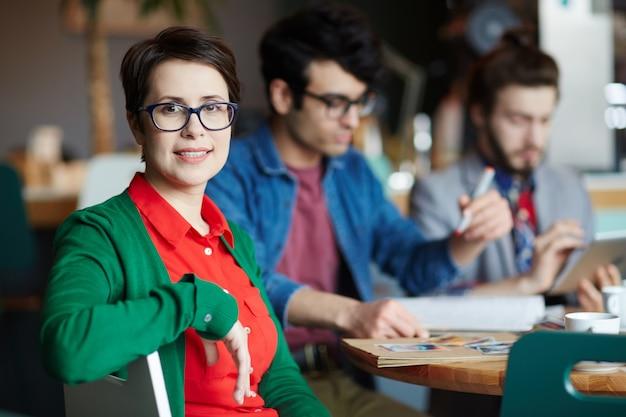 Młoda kreatywnie bizneswoman z kolegami