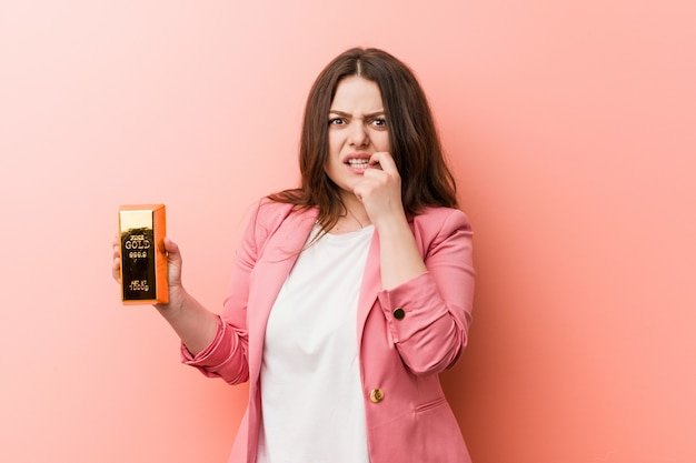 Młoda, kręcona kobieta biznesu plus size ze złotym wlewkiem obgryzającym paznokcie, nerwowa i bardzo niespokojna