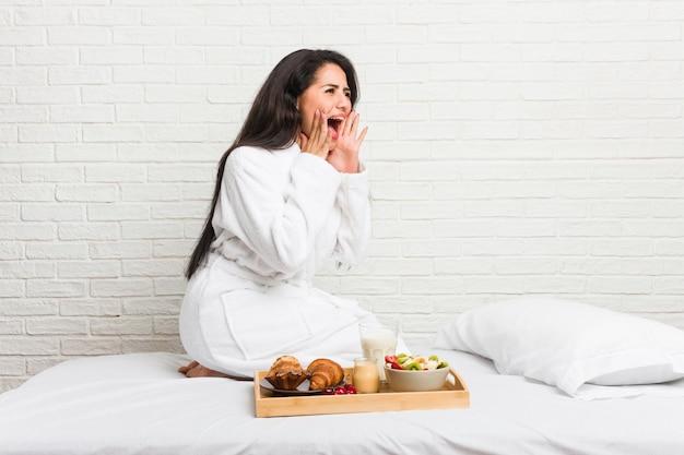 Młoda, kręcona kobieta, która bierze śniadanie, krzyczy głośno, ma otwarte oczy i ręce napięte.