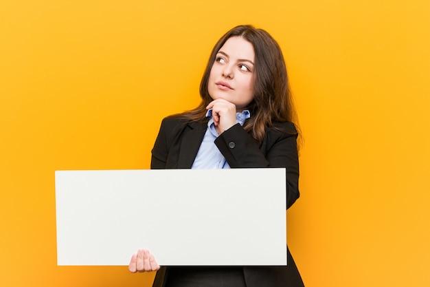 Młoda, kręcona kobieta o dużych rozmiarach, trzymająca plakat wyglądający bokiem z wyrazem wątpliwości i sceptycyzmu.