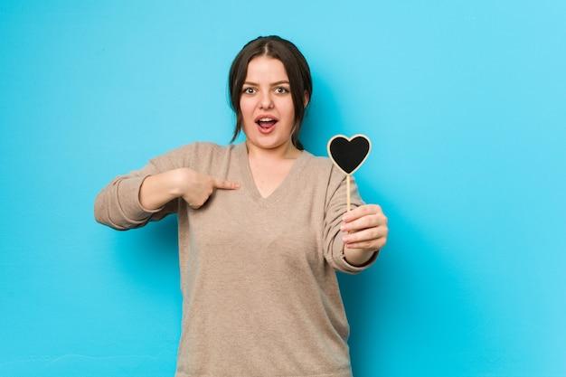 Młoda, kręcona kobieta plus size o kształcie serca zaskoczyła, wskazując na siebie, szeroko się uśmiechając.
