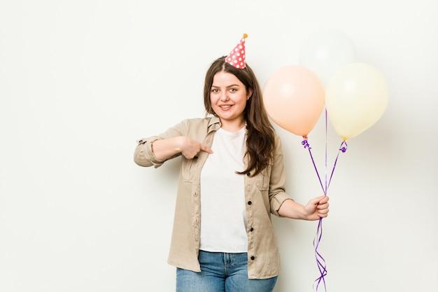 Młoda, kręcona kobieta plus size, obchodząca urodziny, wskazująca ręką na przestrzeń kopii koszuli, dumna i pewna siebie