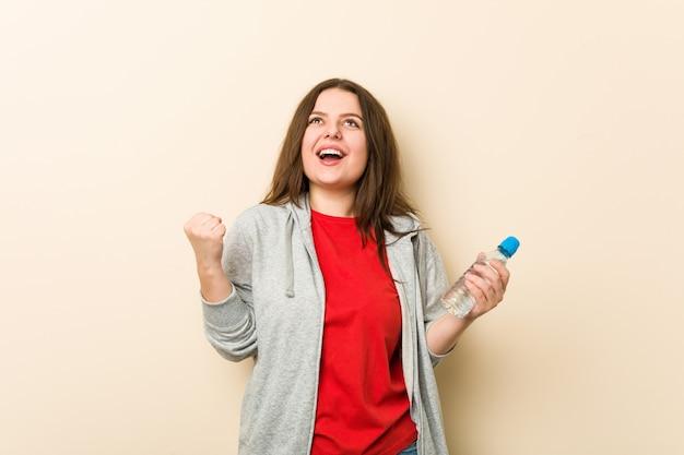 Młoda, kręcona kobieta plus size, trzymając butelkę wody doping beztroski i podekscytowany koncepcja zwycięstwa.