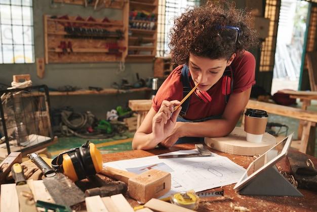 Młoda, kręcona kobieta pochylona nad brudnym stołem i z ołówkiem w ustach przyglądająca się szkicowi z nowym projektem