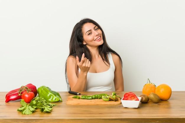 Młoda, kręcona kobieta przygotowuje zdrowy posiłek, wskazując palcem na ciebie, jakby zapraszając podchodzi bliżej.