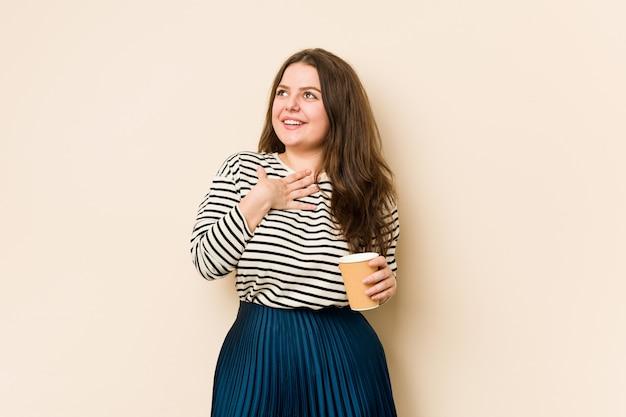 Młoda, kręcona kobieta trzyma kawę, śmieje się głośno, trzymając rękę na piersi.