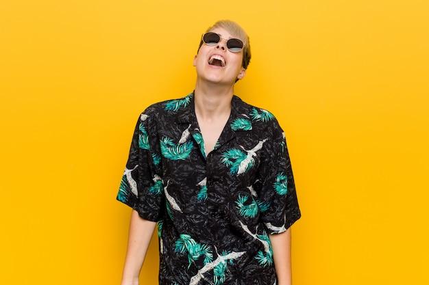 Młoda, kręcona kobieta ubrana w letnią sukienkę, zrelaksowana i szczęśliwa, śmiejąc się, wyciągając szyję pokazując zęby.