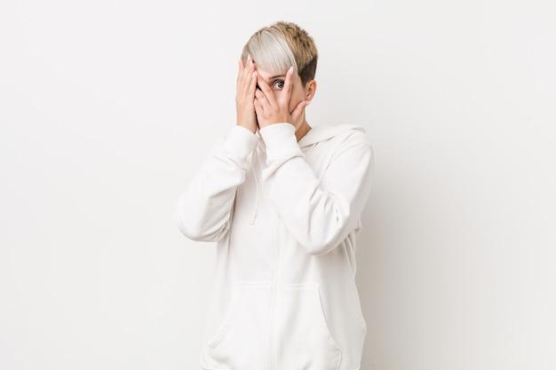 Młoda, kręcona kobieta w białej bluzie z kapturem mruga przez przestraszone i zdenerwowane palce.