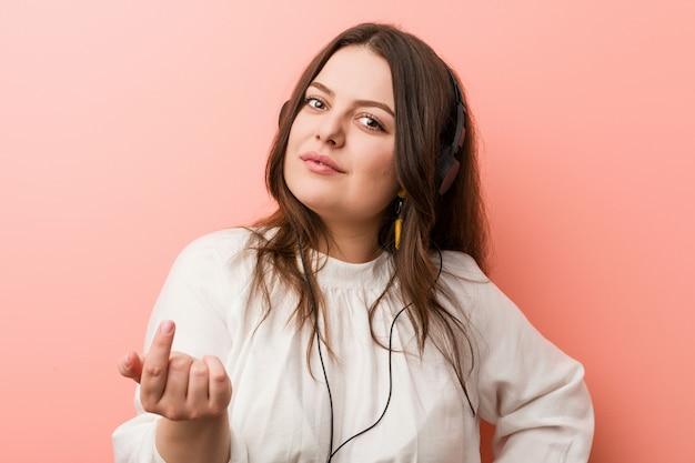 Młoda, kręcona kobieta w dużych rozmiarach, słuchająca muzyki ze słuchawkami wskazującymi na ciebie palcem, jakby zachęcając, podejdź bliżej.