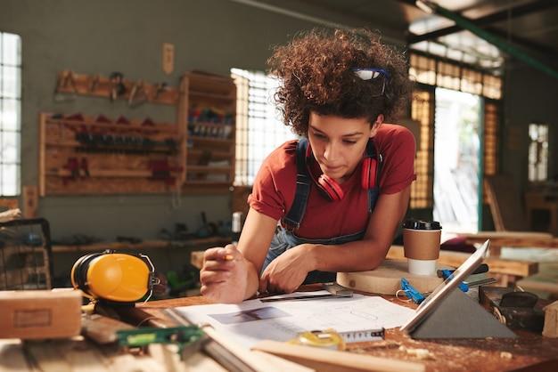 Młoda, kręcona kobieta w dżinsowym kombinezonie pochylona nad brudnym stołem i uważnie przyglądająca się szkicowi, zanim zrobi drewniany stołek