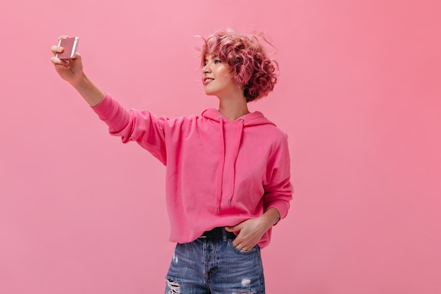 Młoda kręcona kobieta w różowej bluzie z kapturem i dżinsowych szortach robi selfie na białym tle