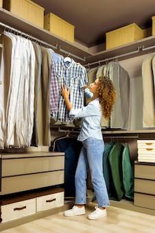 Młoda kręcona kobieta w zwykłych ciuchach wybiera między kraciastymi koszulami na wieszaku, stojąc w garderobie w domu