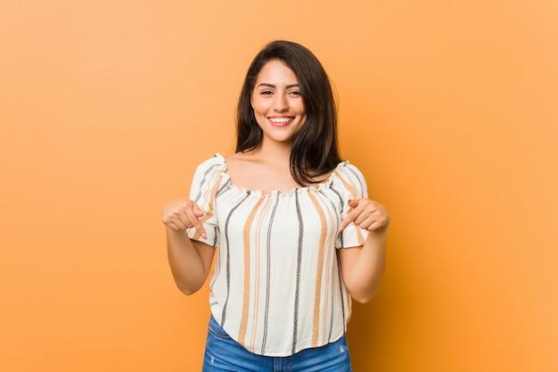 Młoda, kręcona kobieta wskazuje palcami w dół, pozytywne uczucie.