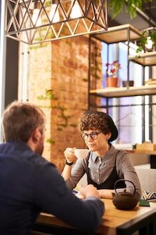 Młoda kręcona stylowa kobieta z filiżanką herbaty siedzi przy stole przed swoim chłopakiem podczas rozmowy w kawiarni