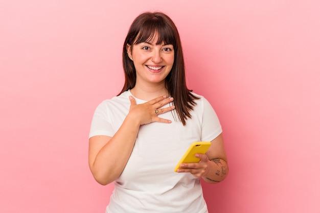 Młoda kręta kobieta kaukaska trzymająca telefon komórkowy na białym tle na różowym tle śmieje się głośno trzymając rękę na klatce piersiowej.