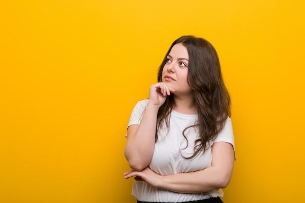 Młoda kręta kobieta plus rozmiar patrzy w bok z wątpliwym i sceptycznym wyrazem twarzy.